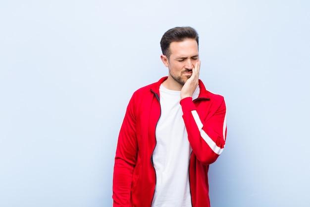 若いハンサムなスポーツ男または頬を保持し、痛みを伴う歯痛に苦しんでいるモニター