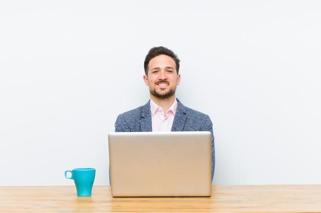 腕を組んで笑って幸せ、誇りと満足の達成者のように見える若いハンサムな実業家