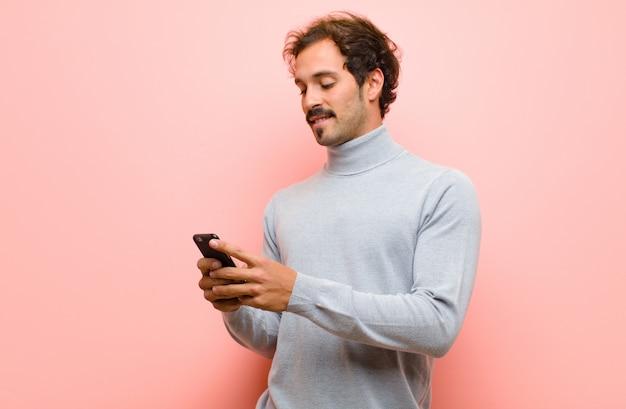 ピンクの平らな壁にスマートフォンで若いハンサムな男