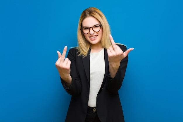 Молодая симпатичная блондинка чувствует себя провокационно, агрессивно и непристойно, переворачивая средний палец, с бунтарским отношением к плоской стене