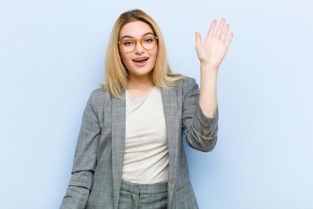 Молодая красивая блондинка улыбается счастливо и весело, машет рукой, приветствует и приветствует вас, или прощается на плоской стене