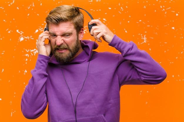 Молодой белокурый мужчина танцует и слушает музыку в наушниках, носить фиолетовый балахон против поврежденной оранжевой стены