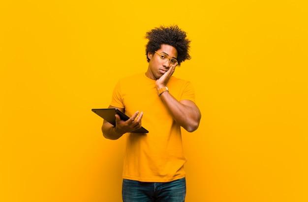 オレンジ色の背景に対してタブレットで若いアフリカ系アメリカ人