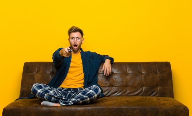 Молодой человек в пижаме и сидя на диване с пультом дистанционного управления