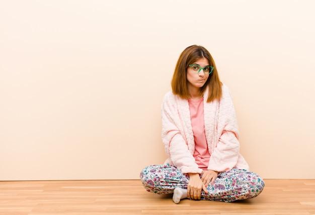自宅で座っているパジャマを着た若い女性は混乱と疑わしい感じ