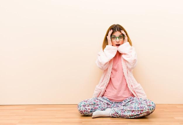 Молодая женщина в пижаме сидит дома в ужасе и шоке