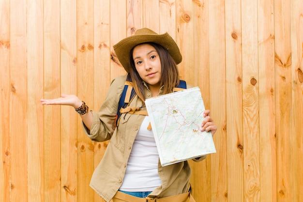 木製の壁に対してマップを持つ若い旅行者女性
