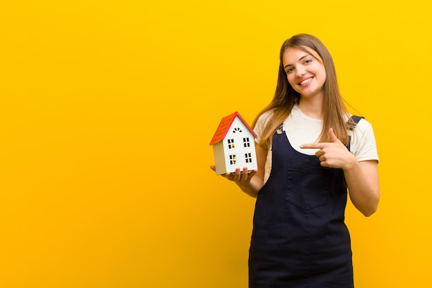 オレンジ色の背景に対して家モデルの若いきれいな女性