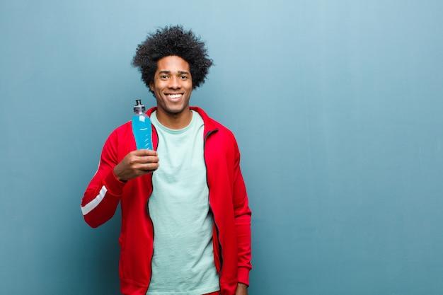 青いグランジ壁にスポーツドリンクを飲みながら若い黒人男性