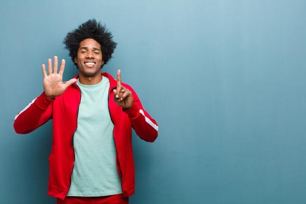 笑みを浮かべて、フレンドリーな探している若い黒のスポーツ男
