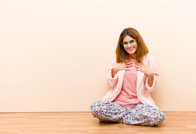 Молодая женщина в пижаме сидит дома, смотрит счастливой, удивленной, гордой и взволнованной, указывая на себя