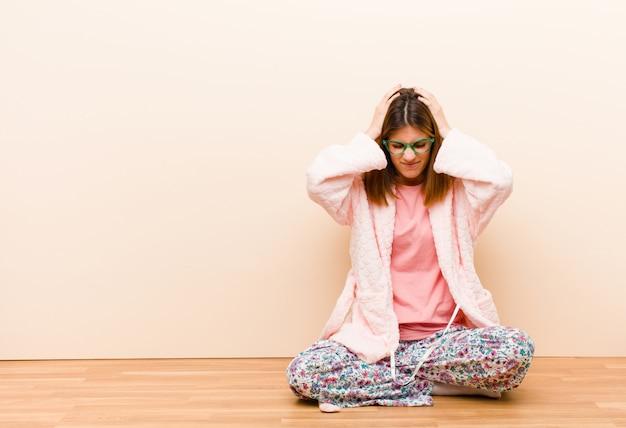 Молодая женщина в пижаме сидит дома, чувствуя стресс и разочарование, поднимая руки к голове, чувствуя усталость, несчастье и мигрень