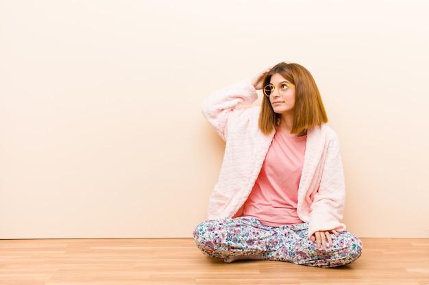 自宅で座っているパジャマを着た若い女性は困惑し、混乱している、頭を掻いて、側にいる感じ