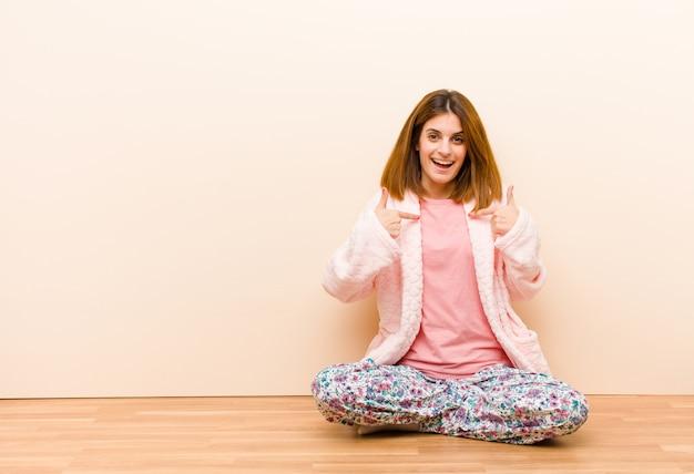 Молодая женщина в пижаме сидит дома, чувствуя себя счастливой, удивленной и гордой, указывая на себя возбужденным, изумленным взглядом