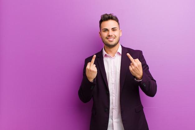 Молодой латиноамериканский мужчина чувствует себя провокационным, агрессивным и непристойным, переворачивая средний палец, с мятежным отношением