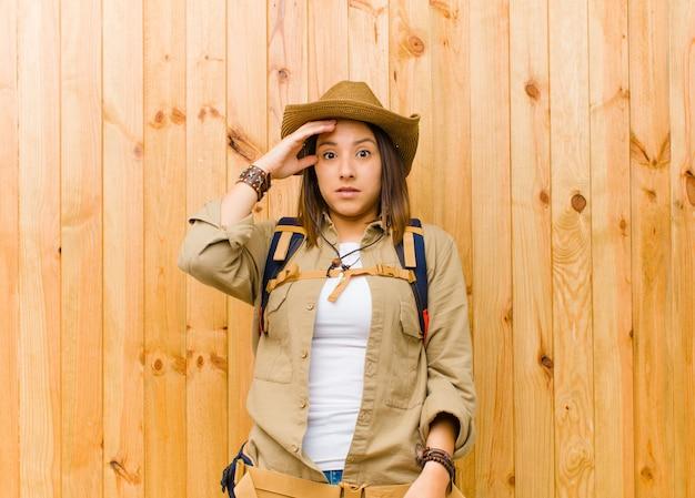 Молодая латинская женщина исследователя против деревянной стены