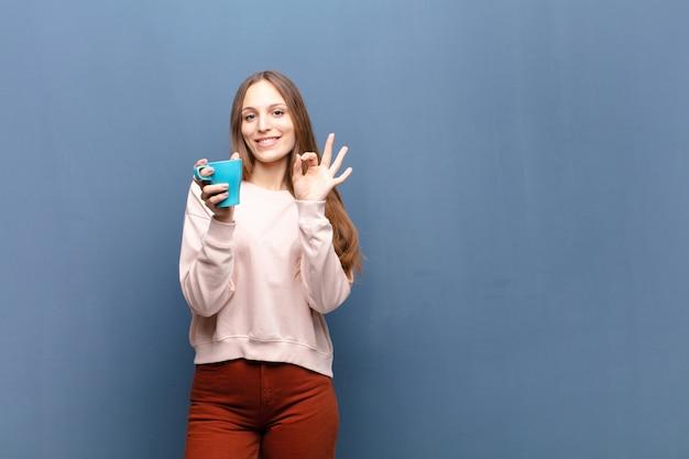 コピースペースで青い壁にコーヒーと若いきれいな女性