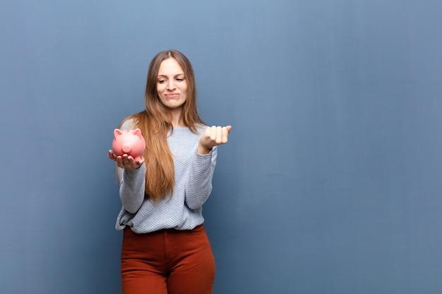 コピースペースで青い壁に貯金箱を持つ若いきれいな女性