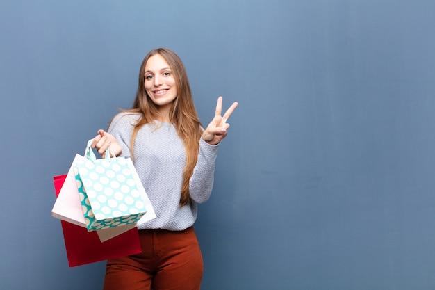 コピースペースで青い壁に買い物袋を持つ若いきれいな女性