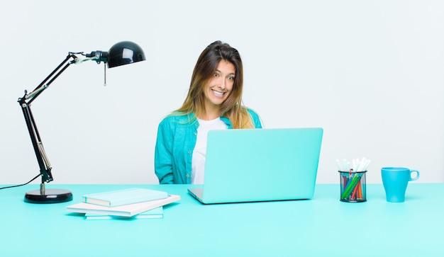Молодая симпатичная женщина, работающая с ноутбуком, выглядит обеспокоенной, подчеркнутой, взволнованной и испуганной, паникуя и стискивая зубы