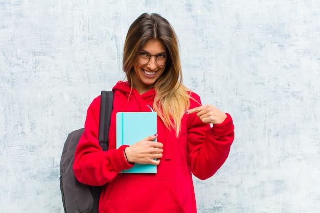 若いきれいな学生の元気でカジュアルな笑顔、下向きと胸を指す