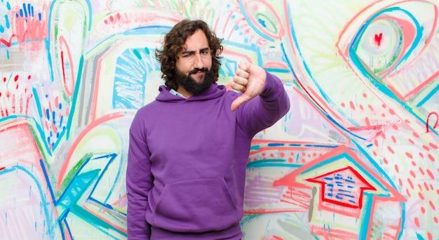 Молодой бородатый сумасшедший, чувствуя, что он сердитый, злой, раздраженный, разочарованный или недовольный, показывает большой палец вниз с серьезным видом на граффити стене