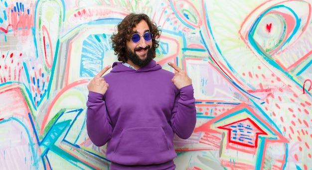 Молодой бородатый сумасшедший, уверенно улыбающийся, указывая на собственную широкую улыбку, позитивное, расслабленное, довольное отношение к граффити стене