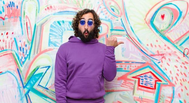 Молодой бородатый сумасшедший смотрит удивленно в неверии, указывая на объект на стороне и говоря вау, невероятно против граффити стены