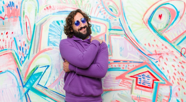 Молодой бородатый сумасшедший чувствует себя влюбленным, улыбается, обнимает и обнимает себя, остается одиноким, эгоистичным и эгоцентричным против граффити стены