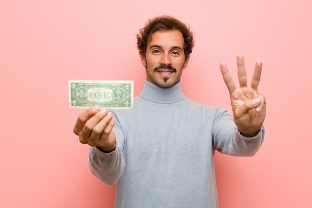ピンクの平らな壁にドル紙幣で若いハンサムな男