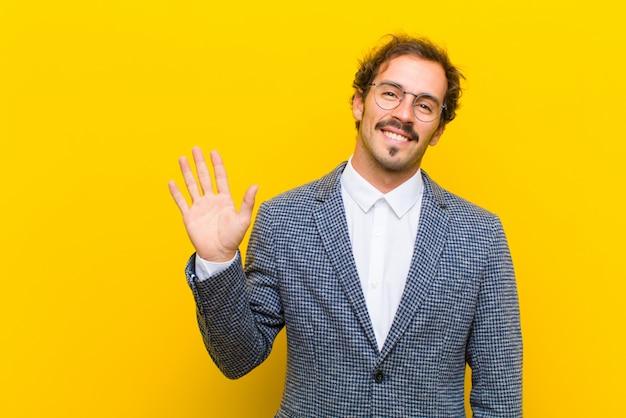 幸せで元気な笑顔、手を振って、歓迎と挨拶、またはオレンジ色の壁に別れを告げる若いハンサムな男