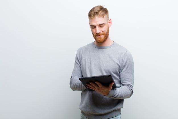 Молодой рыжий мужчина держит планшет на белом фоне
