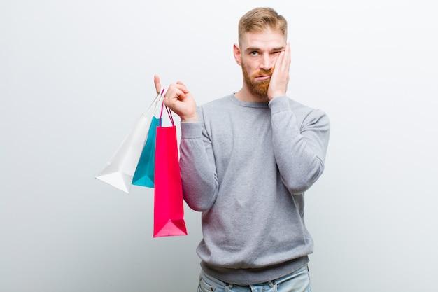 白い背景の買い物袋を持つ若い赤い頭の男