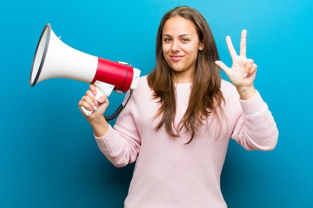 Молодая женщина с мегафоном на синем фоне