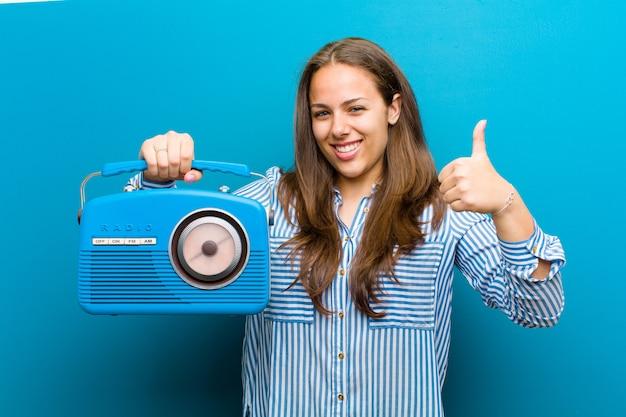 青い背景のビンテージラジオを持つ若い女性