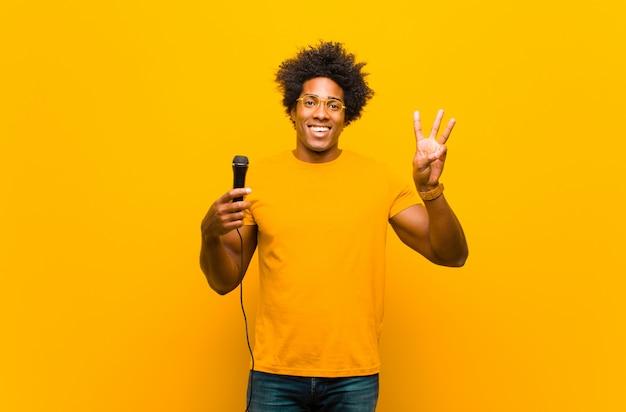 Молодой афроамериканец человек с микрофоном петь против или