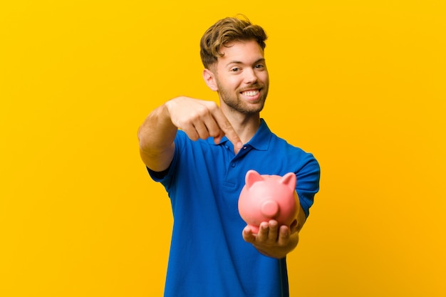オレンジ色の背景に対して貯金箱と若い男