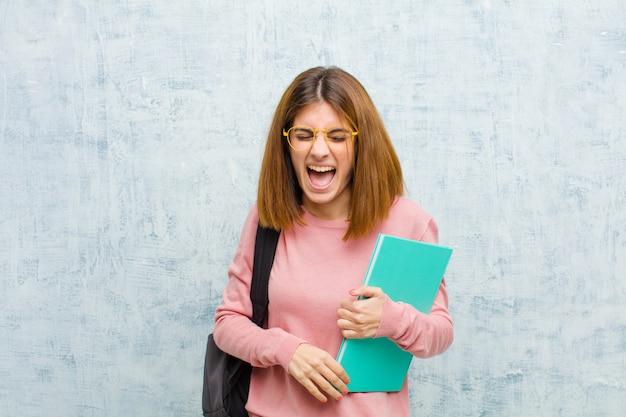若い学生の女性が積極的に叫んで、非常に怒って、イライラして、激怒またはイライラして、グランジの壁を背景にノーと叫んで