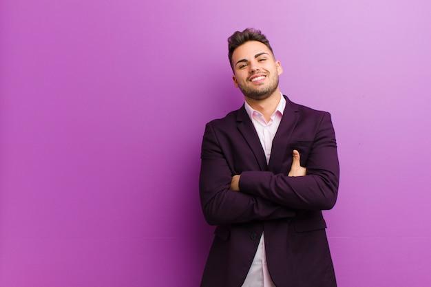 Молодой латиноамериканский человек счастливо смеется со скрещенными руками, в расслабленной, позитивной и удовлетворенной позе