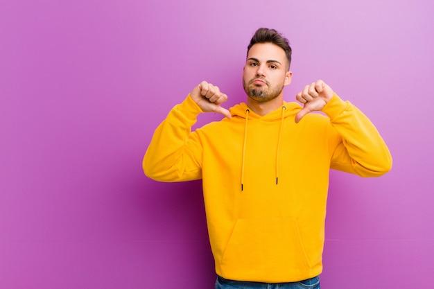 Молодой испанец человек с случайным взглядом на фиолетовом фоне