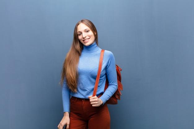 Молодая милая женщина против голубой стены с космосом экземпляра