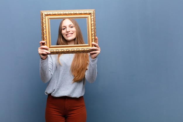 Молодая милая женщина с барочной рамкой против голубой стены с космосом экземпляра