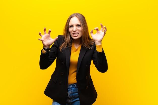 Молодая красивая деловая женщина кричит в панике или гневе, шокирована, испугана или в ярости