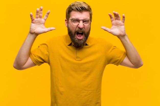 Молодой блондин человек кричит в панике или гневе, шокирован, испуган или в ярости