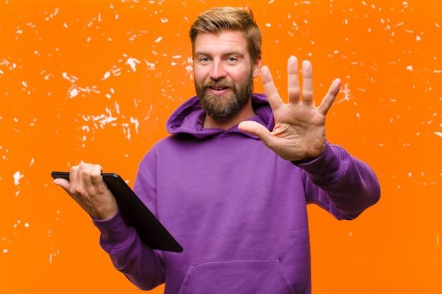 Молодой блондин человек с планшетом, носить фиолетовый балахон против поврежденной оранжевой стены