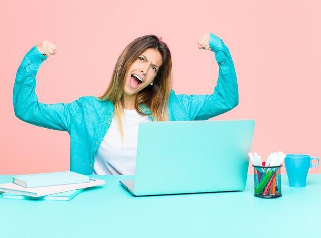 Молодая красивая женщина работает с ноутбуком, торжествующе крича, выглядит как возбужденный, счастливый и удивленный победитель, празднуя