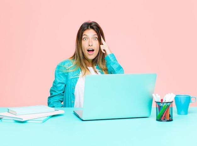 驚き、口を開けて、ショックを受けて、新しい思考、アイデアや概念を実現するラップトップで働く若いきれいな女性