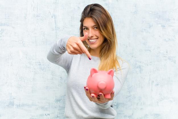 グランジの壁に貯金箱と若いきれいな女性