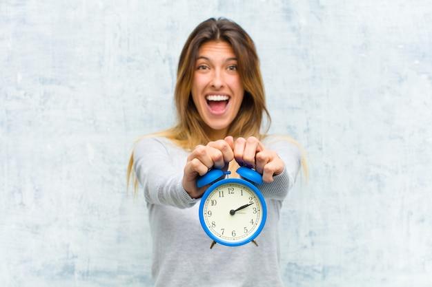 グランジの壁に目覚まし時計で若いきれいな女性