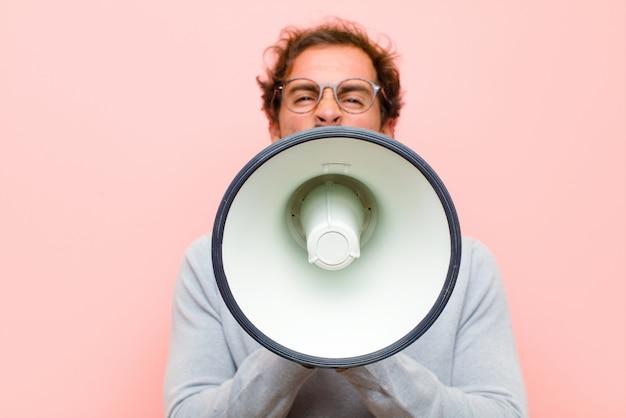Молодой красавец с мегафоном на розовой плоской стене
